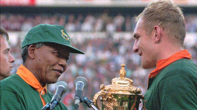 FILE - In this June 24, 1995 file photo, South African rugby captain Francios Pienaar, right, receives the Rugby World Cup from South African President Nelson Mandela, left, who wears a South African rugby shirt, after they defeated New Zealand in the final 15-12 at Ellis Park, Johannesburg. South Africa's President Jacob Zuma said, Thursday, Dec. 5, 2013, that Mandela has died. He was 95. (AP Photo/Ross Setford, File)
