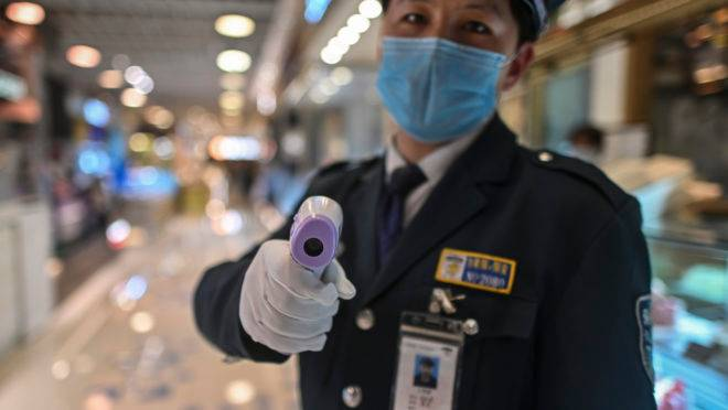 A guard wearing a facemask amid concerns over the spread of the COVID-19 novel coronavirus, holds a thermal gun to check the body temperature of visitors at the entrance of a restaurant area in Shanghai, on March 21, 2020. (Photo by Hector RETAMAL / AFP)