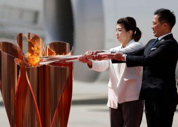 Três medalhistas olímpicos de ouro Tadahiro Nomura e Saori Yoshida acendem a Chama Olímpica no caldeirão olímpico durante uma cerimônia na Base de Matsushima da Força Aérea de Autodefesa do Japão em Higashi-Matsuhsima, prefeitura de Miyagi, norte do Japão em 20 de março de 2020.