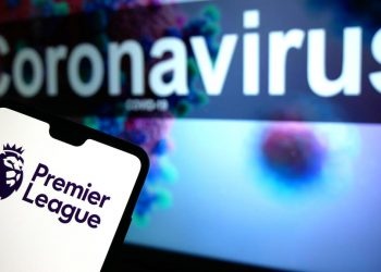 Coronavirus Stock The Premier League logo seen displayed on a mobile phone with an illustrative model of the Coronavirus displayed on a monitor in the background. Photo credit should read: James Warwick/EMPICS Entertainment PUBLICATIONxINxGERxSUIxAUTxONLY Copyright: xJamesxWarwickx 53182901