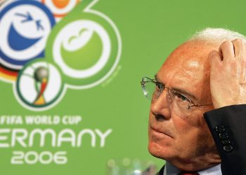 FILE - In this March 6, 2006 file photo German soccer legend Franz Beckenbauer gestures in front of the logo of the soccer world cup 2006 taking place in Germany during the FIFA team workshop in Duesseldorf, western Germany. Pressure is growing on Franz Beckenbauer to speak on the latest corruption allegations surrounding the 2006 World Cup in Germany. (AP Photo/Frank Augstein, file)