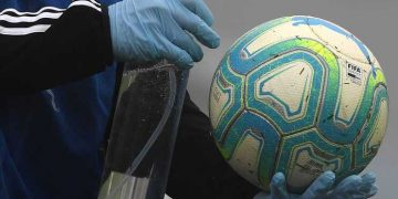 A ball boy disinfects a ball during a Uruguayan tournament football match between Nacional and Penarol at the Centenario stadium in Montevideo on August 9, 2020, amid the COVID-19 novel coronavirus pandemic. - The match is played behind closed doors as a preventive measure against the spread of COVID-19. (Photo by Pablo PORCIUNCULA / AFP)
