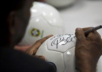Brazilian football legend Edson Arantes do Nascimento, known as Pele, signs a ball during a press conference at Volkswagen plant in Sao Bernardo do Campo, in the metropolitan area of Sao Paulo, Brazil, on June 10, 2013. AFP PHOTO / Nelson ALMEIDA (Photo credit should read NELSON ALMEIDA/AFP via Getty Images)