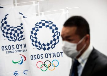 """(FILES) In this file photo taken on March 11, 2020 a reporter wearing a face mask stands next to the banners of the Tokyo Olympic Games during a Tokyo 2020 press conference about the spread of the new coronavirus in Tokyo. - Japan has asked for a one-year postponement of the Tokyo 2020 Games over the global coronavirus pandemic, and the International Olympic Committee has agreed, the country's prime minister said on March 24, 2020. """"I proposed to postpone for about a year and president Bach responded with 100 percent agreement,"""" Shinzo Abe told reporters referring to Thomas Bach, head of the IOC. (Photo by Behrouz MEHRI / AFP)"""