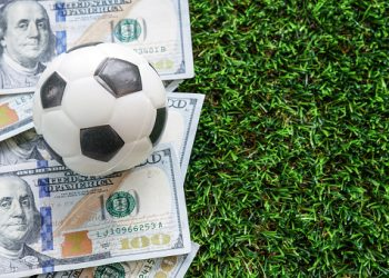 Football Business Concept : A fooball on dollar bills and green grass background. Soccer gambling money concept. With copy space.
