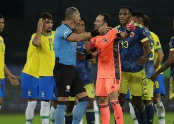 Colombia's goalkeeper David Ospina, center, complains to Referee Nestor Pitana, of Argentina, during a Copa America soccer match against Brazil at Nilton Santos stadium in Rio de Janeiro, Brazil, Wednesday, June 23, 2021. (AP Photo/Silvia Izquierdo)